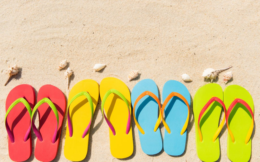 Four pairs of flip flops in a row on beach
